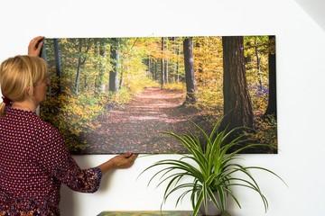 Frau dekoriert eine Fotoleinwand