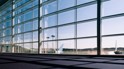 Poster Airport Walkway and glass curtain wall with Airplane background at Airport terminal, Travel concept with copy space. Silhouette background