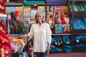 Mature woman smiling while working in her fabric shop