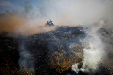 A tractor drives in a smoking field during a fire in an area where Palestinians have been causing blazes by flying kites and balloons loaded with flammable materials, on the Israeli side of the border between Israel and the Gaza Strip, near kibbutz Nir Am
