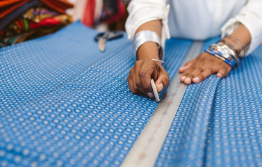 Closeup of a woman measuring textiles in her fabric shop