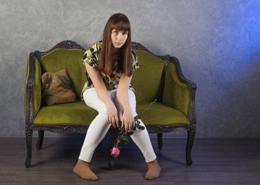 Sad teenage girl sits on green sofa. On gray background. Studio.