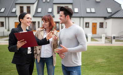 Young couple with real estate agent visiting house for sale in residential area
