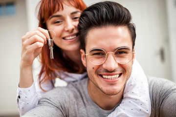 Smiling couple with keys to their new home hugging and looking at camera taking selfie