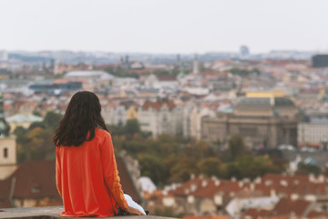 Young girl looking at the Old Town in European city Prague from observation deck