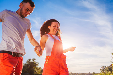 Young man and woman running on blue sky background. Couple having fun at sunset. Summer holidays Wall mural