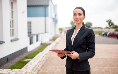 Real estate agent in front of house for sale ready to presenting offer, copy space