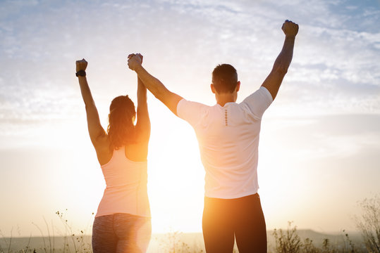 Back view of couple young of athletes with arms up towards the sunset. Sporty man and woman celebrating running outdoor training success.