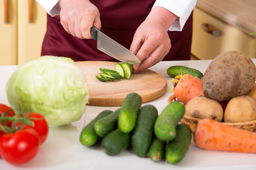 Preparation of vegetable salad. Close-up of a man's hand with a knife chopped cucumber.