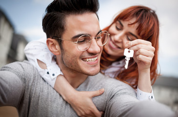 Loving couple with keys to their new home hugging and looking at camera taking selfie