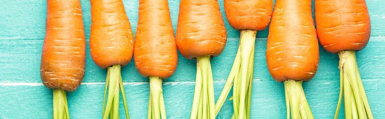 carrots on a blue wooden background, fresh vegetables, carotene, banner