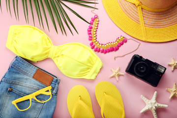 Yellow swimsuit with jeans and green palm leaf on pink background