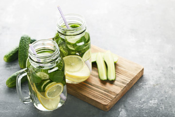 Wall Mural - Lemonade with cucumbers, lemons and mint leafs in glass jars on wooden table