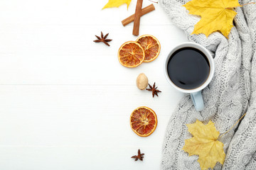 Cup of coffee with dried oranges and leafs on wooden table