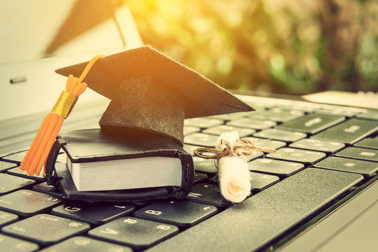 online learning or e-learning and online graduate certificate program concept : Black graduation cap, diploma on a laptop computer keyboard, depicts distant learning can be done via cyber / internet