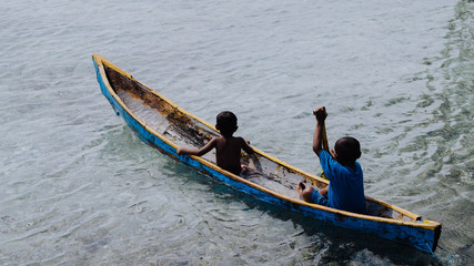 Silhouette of two local boys in a boat on Arborek Island in Raja Ampat, West Papua, Indonesia, near the famous Manta Point dive spot