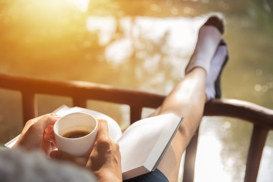 Happy Woman sitting and holding cup of hot coffee.