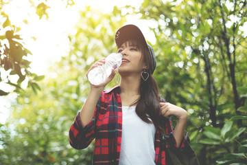 Asian girl traveler in red plaid shirt drinking water.