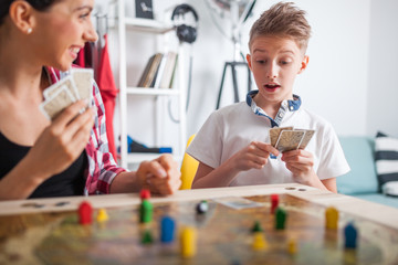 Mother and son playing modern board game in teenage room at home