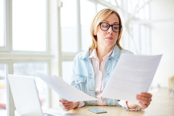 Adult woman in glasses sitting with gadgets at table and reading papers with concentration while working