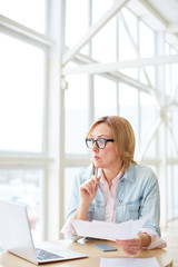 Thoughtful woman in glasses holding pen with papers and looking away in brainstorming sitting with laptop at table