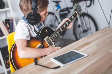Kid boy learning to play electric guitar using tablet with headphones