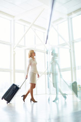 Side view of elegant woman standing with suitcase reflecting in glass wall inside of light hall.