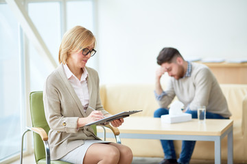 Elegant woman taking notes on clipboard while conducting therapy with upset man having mental problems