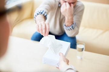 Faceless shot of psychiatrist giving box of tissues to man having consultation and feeling depressed