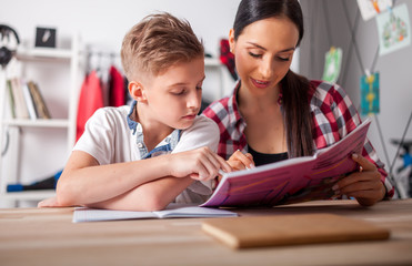 Mother helping her son with homework in teenage room at home