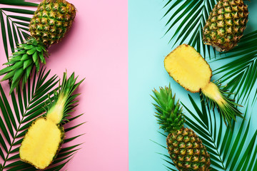 Pineapples, palm leaves on pastel colorful pink and turquoise background with copy space. Creative...