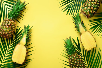 Pineapples and tropical palm leaves on punchy pastel yellow background. Summer concept. Creative flat lay with copy space. Top view