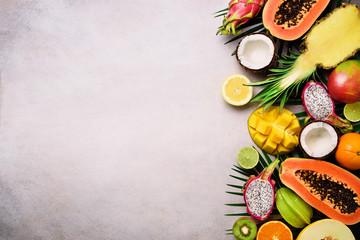 Exotic fruits and tropical palm leaves on grey concrete, background - papaya, mango, pineapple, banana, carambola, dragon fruit, kiwi, lemon, orange, melon, coconut, lime. Top view.