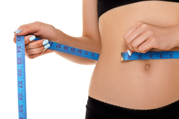 woman measuring waist with blue measuring tape.