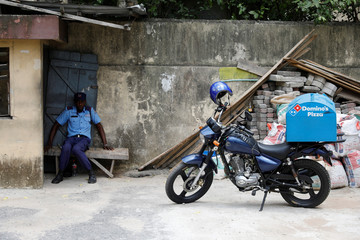 A private security guard sits on a broken bench as a delivery motorbike is parked in front of a building in Ikeja district