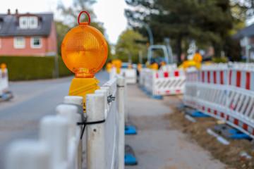 rote und weiße Barrikaden mit Warnlichtern an einer Straße in einem Wohngebiet