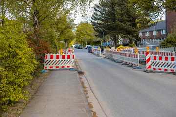 Baustelle an einem Fußgängerweg, mit orangenen Warnlampen beleuchtete Barrikaden blockieren den Gehweg