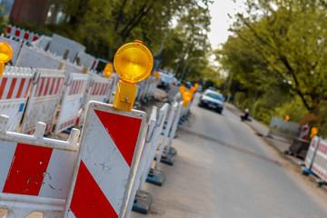 Baustelle an einem Fußgängerweg, beleuchtete Barrikaden blockieren den Gehweg