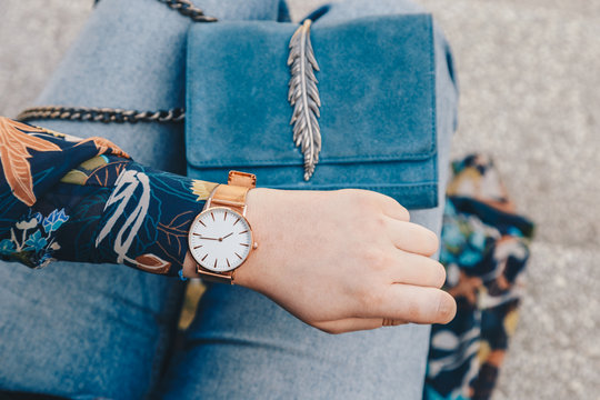Stylish woman checking time on her elegant rose gold wrist watch