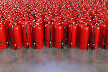 A lot of fire extinguishers on a grey background.