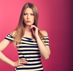 Angry unhappy suspicious thinking woman in striped dress looking on bright pink background. Toned closeup portrait