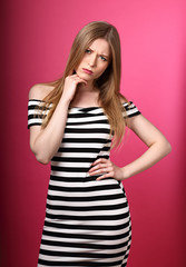 Angry unhappy suspicious woman in striped dress looking with hand under the face on pink background