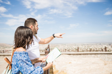 Couple of travelers using map for sightseeing in town