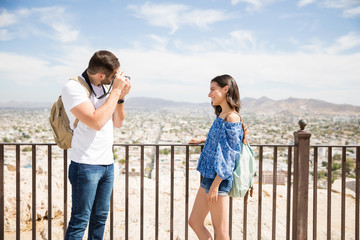 Boyfriend clicking a picture with camera of an smiling girlfriend
