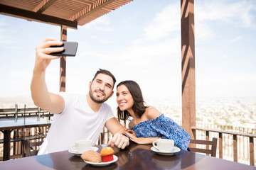Latin couple taking selfie while sitting in cafe outdoors