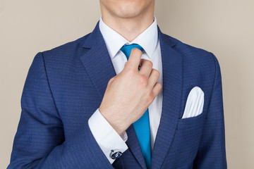 Close up cropped portrait of young handsome businessman in suit. He is fixing his tie. He stands on pure light background