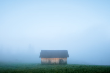 Mountain valley during sunrise. Alone house on foggy meadow. Located place: Carpathians, Ukraine, Europe