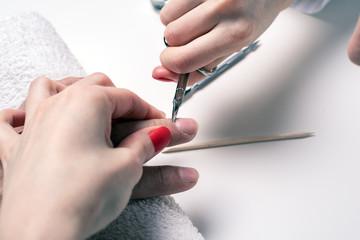 Men's manicure. woman beautician treats cuticles of dry male hands