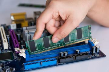 Wall Mural - Technician installing RAM stick (random access memory) to socket on motherboard