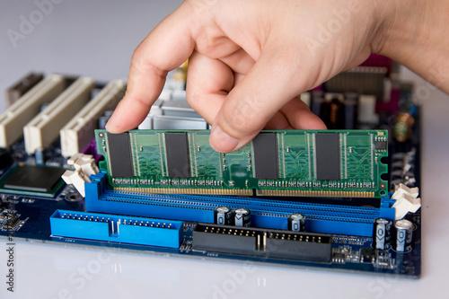Wall mural Technician installing RAM stick (random access memory) to socket on motherboard